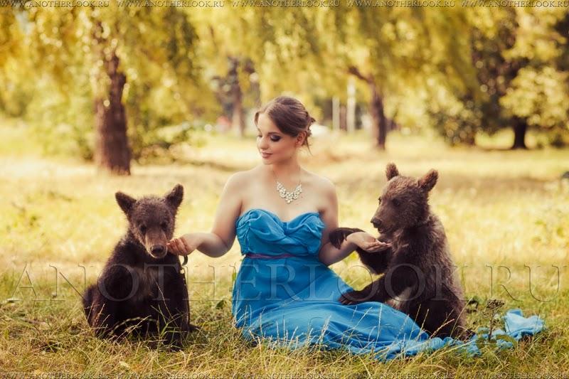 Девушка кормит с рук двух маленьких медвежат