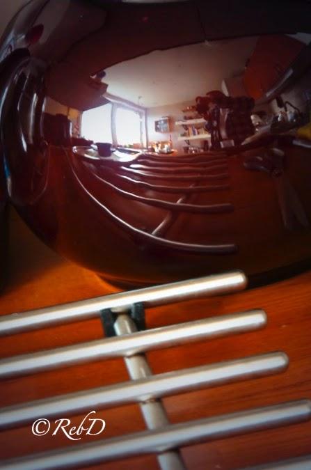 Fotografen speglad i en rund, brun tekanna. foto: Reb Dutius