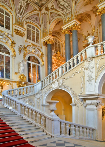 red carpeted jordan staircase with gold work in winter palace or hermitage museum in st.petersburg russia