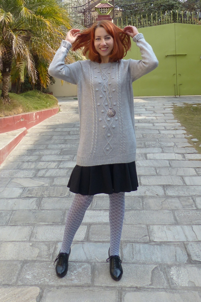 Grey sweater dress worn with black skirt and printed tights