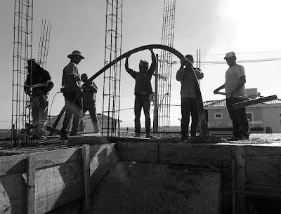 Operários concretam a laje de uma casa em construção (foto: Jean Tosetto).