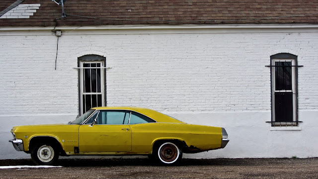 A yellow Impala parked by a brick wall near downtown Denver.