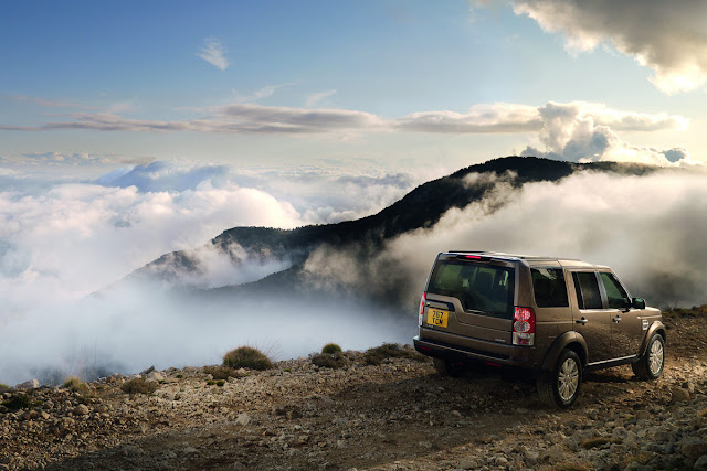 Rear 3/4 view of bronze 2011 Land Rover LR4 on dirt trail above mountains with fog and clouds