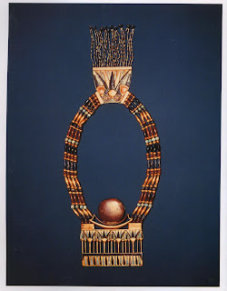 Lunar pectoral with necklace of carnelian, lapis lazuli, feldspar; and gold beads and a lotus blossom counterpoise. This is a striking example of the three basic components in Egyptian jewelry —pectoral, beaded neck-lace, and counterpoise—unified into a single design. Even the beaded tassels hanging from the counterpoise acted as amulets, protecting the wearer from behind. This piece was worn by King Tutankhamen and buried in his tomb at Thebes, c. 1352 B. c Pectoral; width, /1.8 cm. Cairo Museum
