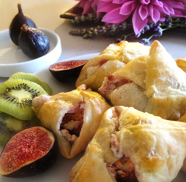 Image of Puff Pastries on a plate with fresh figs and kiwi fruit. The fresh figs and chèvre can be seen int he openingsof the pastries