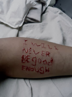 Cutter cuts the words I will never be good enough on his arm