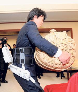 SEORANG pekerja Cyberdyne mengangkat beg jerami yang mengandungi beras seberat 65 kilogram di sebuah pejabat di Niigata semalam.