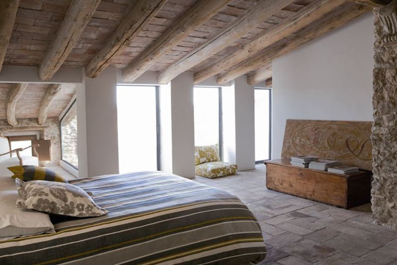 Loft bedroom with wood ceiling, exposed beams, a stone wall nook and simple furnishings