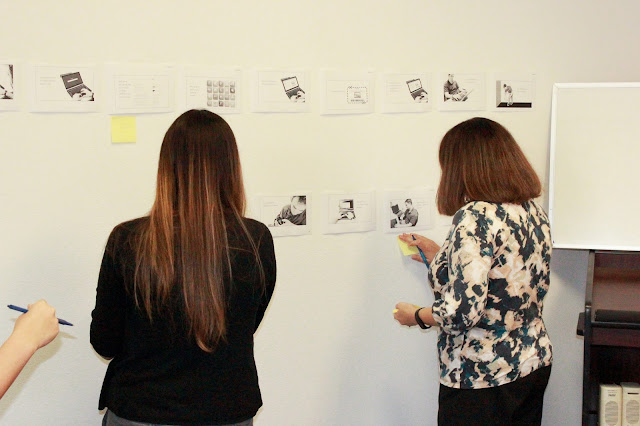 Three women putting post it notes on a wall