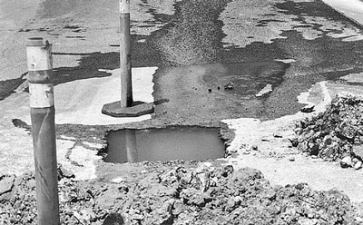 Groundwater exiting a test pit excavated into a pavement.