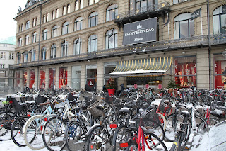 lots of bikes bicycles snow outside Magazine shopping centre in Copenhagen Knogens Nytorv winter