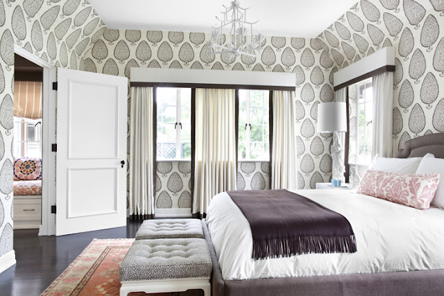 master bedroom in a Tudor home in Beverly Hills with Katie Ridder wallpaper, ottoman at the foot of the bed, Turkish rug and white curtains