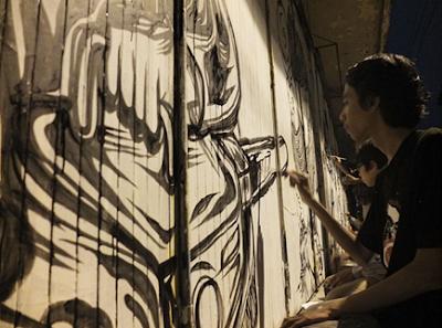 seniman mural sedang melukis sebuah toko di kota Yogyakarta