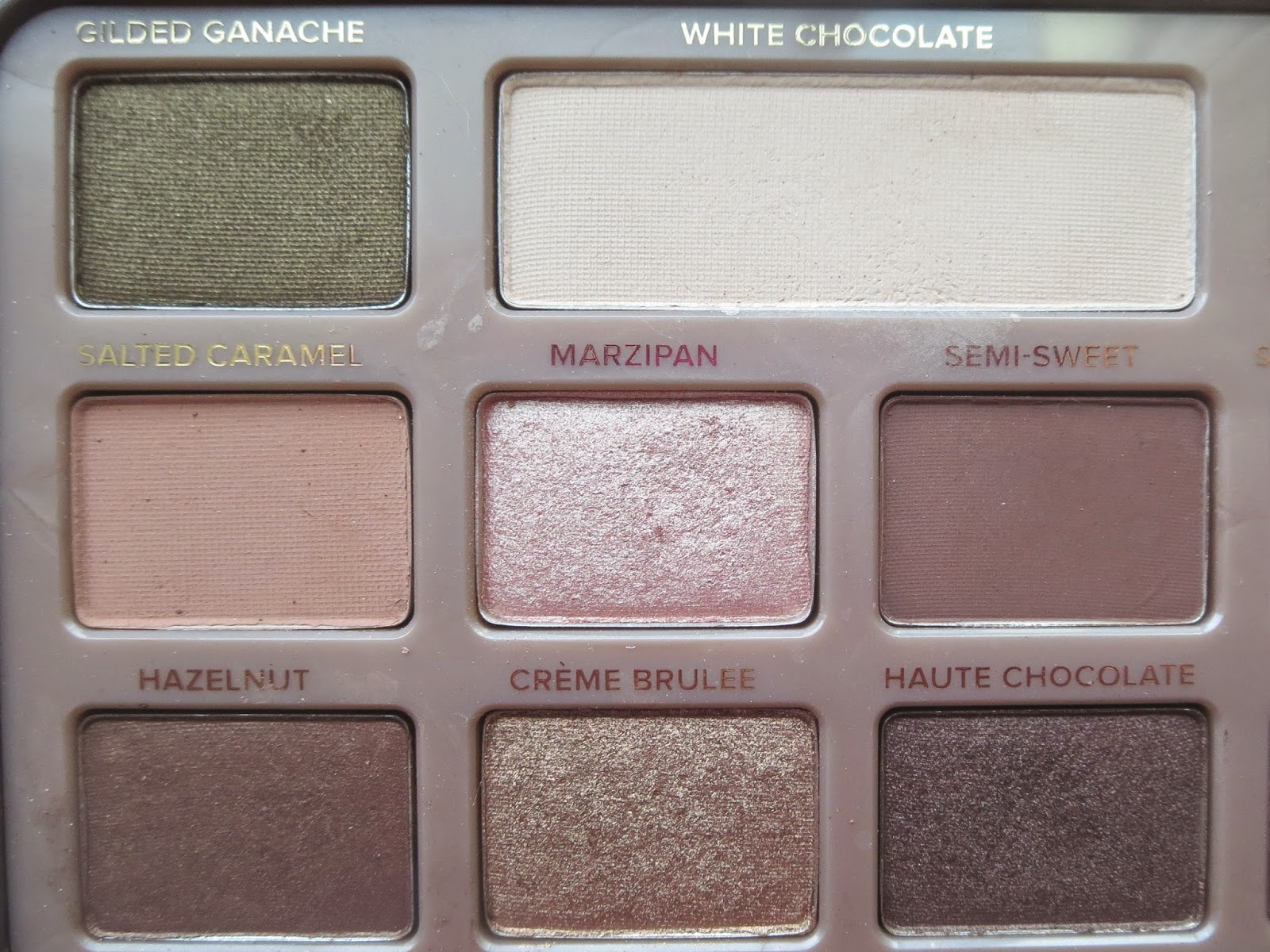 a picture of Too Faced Chocolate Bar ; Haute Chocolate, Semi-Sweet, Creme Brulee, Marzipan, White Chocolate, Hazelnut, Salted Caramel, Gilded Ganache