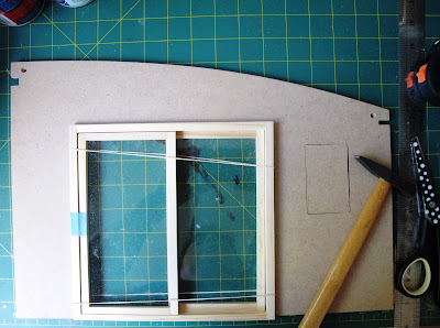 Side wall of a dolls house kit, with a hole cut for the sliding doors (which are in the hole) and a piece of wood inserted into a previously-cut window opening.