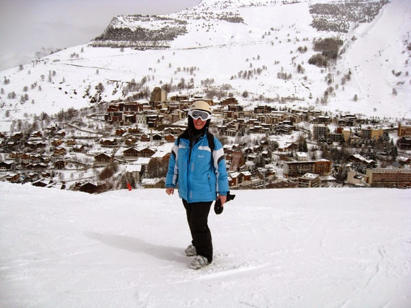 In ski gear posing on mountain with ski village in the background