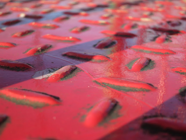 Red painted metal surface at top of a slide. Nothing more.