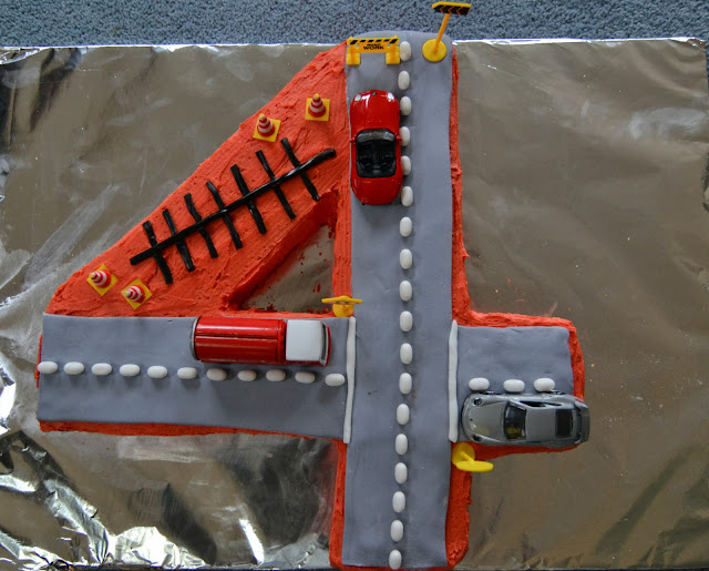 4 shaped birthday cake with road theme