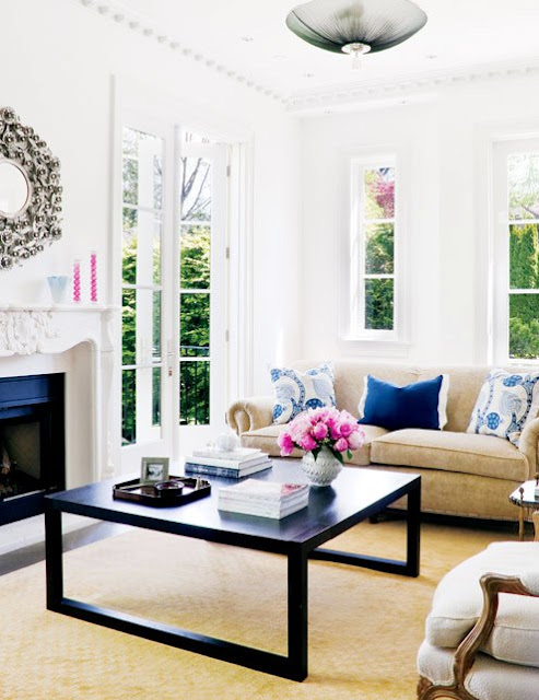 living room with French doors, a neutral sofa with blue accent pillows, a fireplace with molded mantel with a round mirror above it, a Louis XIV chair and a dark wood coffee table