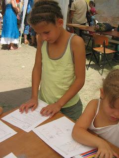 Az előbbi kislányok a képen. A kicsi már önállóan dolgozik az előtte levő papíron, épp színt keres magának. A nagy mellette áll, és olvasgatja a neki való feladatlapot.