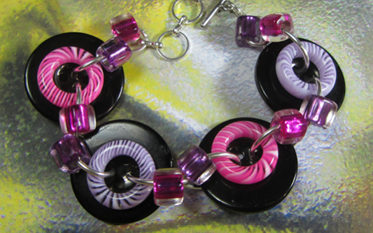 Bold button bracelet has big black buttons accented with donut beads and smaller shiny beads