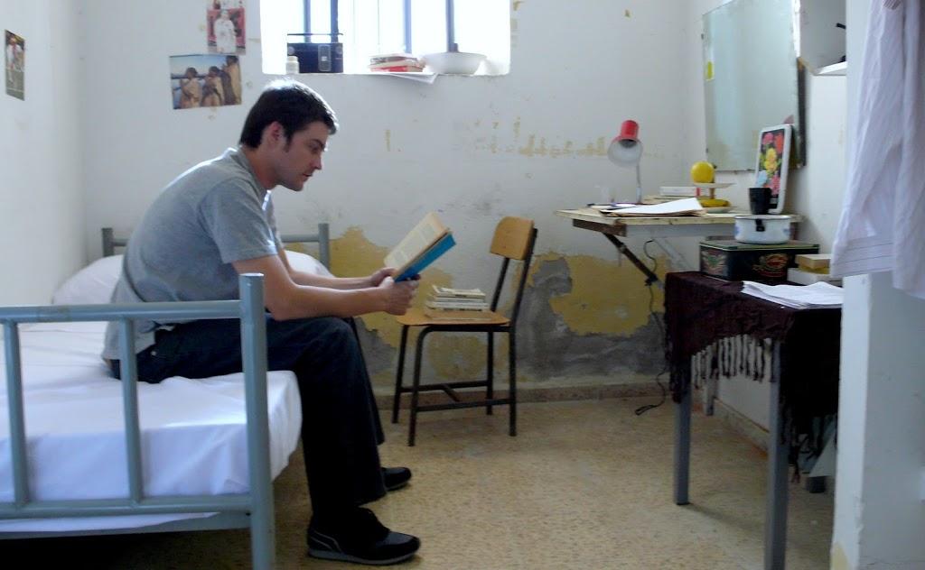 fotograma con Roger Coma en la cárcel leyendo un libro. en la imagen se potencian los tonos fríos