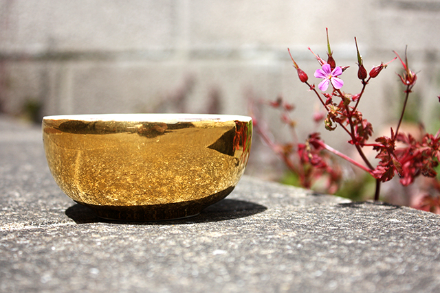 gold bowl next to small purple flower