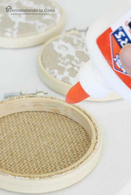 Elmer's glue on the back of hoop to hold the fabric