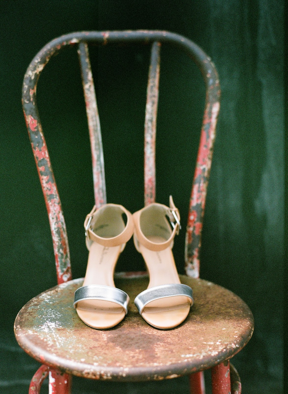 minimal silver wedding shoes on an antique chair with a green backdrop on a brooklyn, new york rooftop