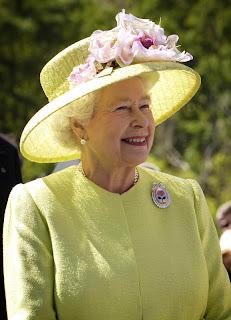 Queen Elizabeth, toujours coquette, bien que légèrement trop fardée, porte une très belle robe citron vert