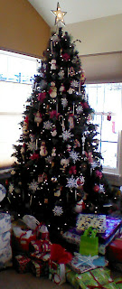 artificial green decorated christmas tree with gifts at bottom