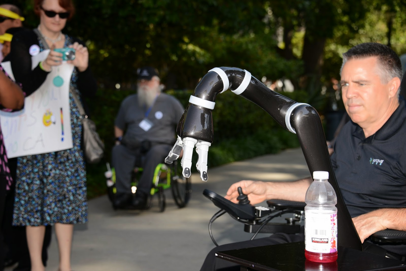 a man using a power wheelchair uses the JACO robotic arm device to reach for a bottled beverage.
