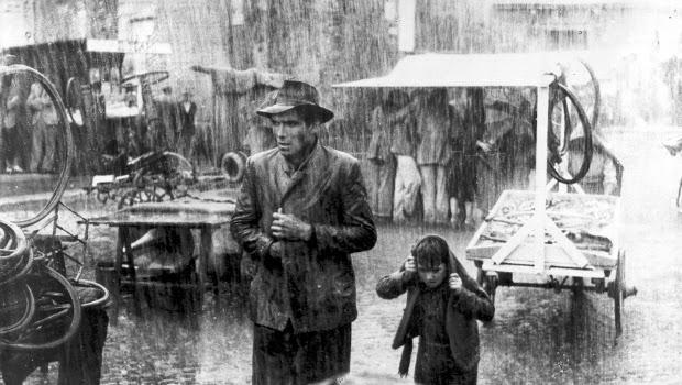Fotograma de la película, Ladrón de bicicletas. Llueve en Roma, padre e hijo observan unas bicicletas