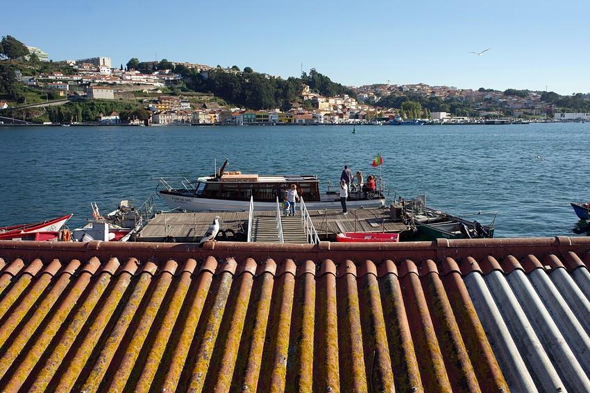 Vista sobre o cais de Lordelo com o barco ancorado e algumas pessoas a sairem. Em Primeiro plano um telhado e ao fundo, após o rio a margem do lugar piscatório da Afurada