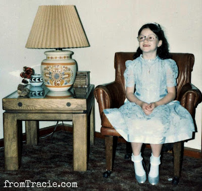 Tracie as little girl wearing glasses