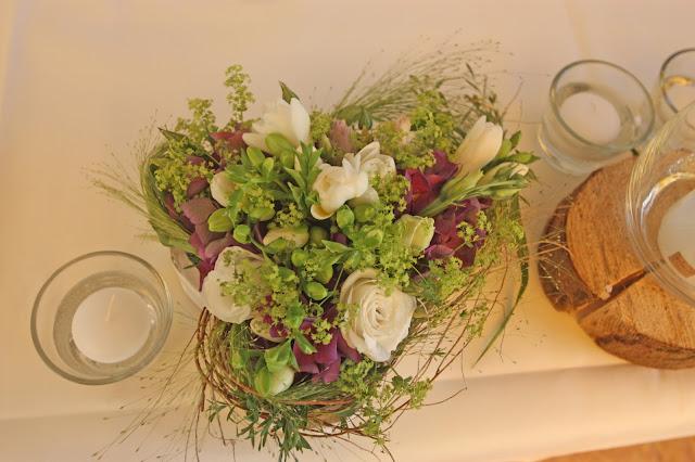 Herzförmige Tischgestecke mit Fresien, Gräsern und lila Akzenten