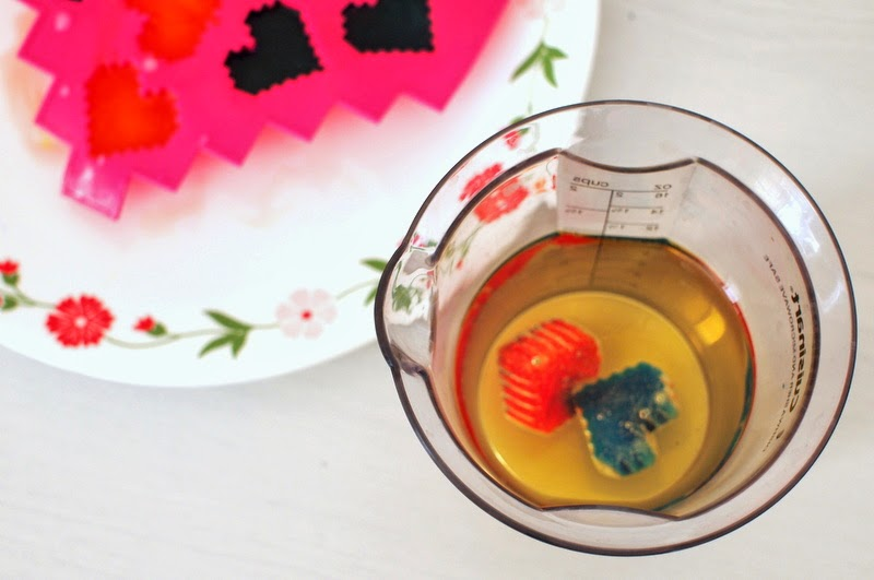 place colored ice cubes in cooking oil