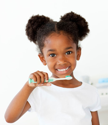 African American child brushing her teeth