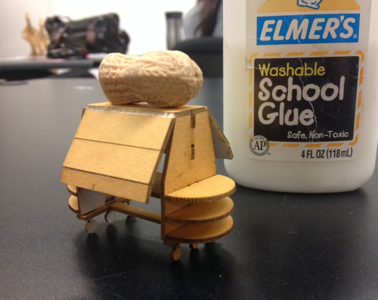 Image shows side view of a wooden miniature kiosk model with a peanut eraser on top and Elmer's glue next to it.