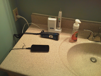 Three devices plugged into the power strip: electric toothbrush, electric razor, and cellphone.