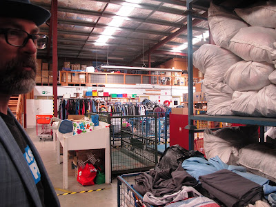 Man standing next to a pallet rack full of bags of clothing in a large warehouse.