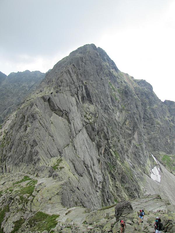 Zmarzła Przełęcz (2126 m n.p.m.), a za nią Zamarła Turnia (2179 m n.p.m.) z gładkimi  południowymi ścianami, a dalej góruje Kozi Wierch (słow. Kozí vrch, 2291 m n.p.m.).