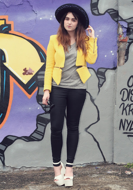 uk fashion style, yellow blazer from zara, grey all saints tee, black leather look verne ashby jeans from all saints styled with white platform wedges and a large brim woolen black hat, chic look with flower sunglasses embellished with black roses. graffiti  wall background