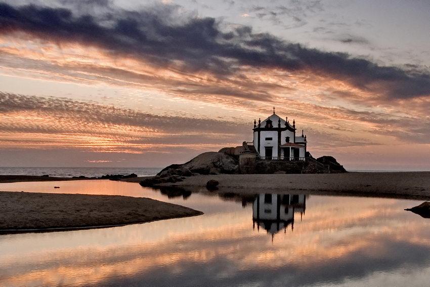 Apontamento ao entardecer com o céu cor de fogo e a capela reflectida no lago do riacho