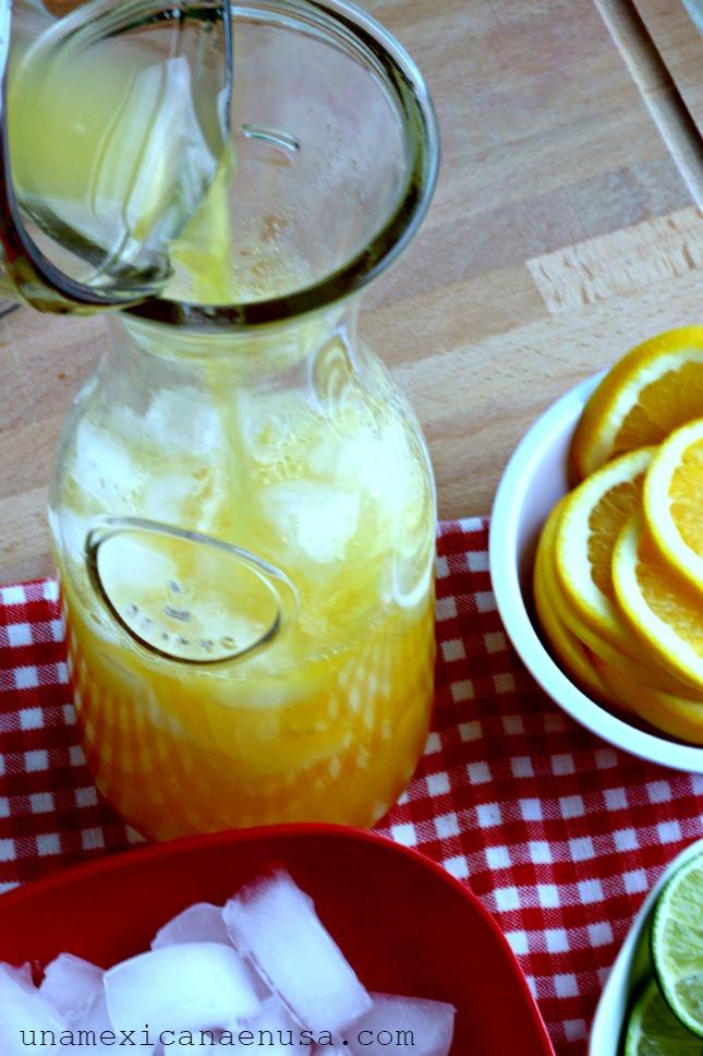 Garrafa con hielo y jugos de mandarina, limón y naranja.