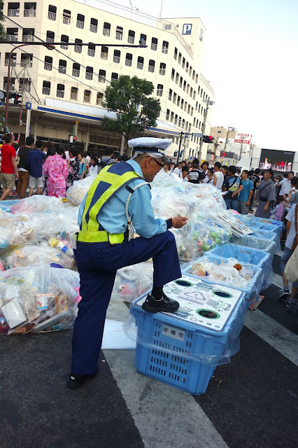 Japanese policeman guarding trash