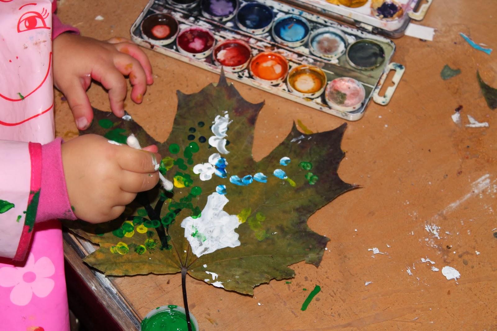 Алиса рисует на осенних листьях