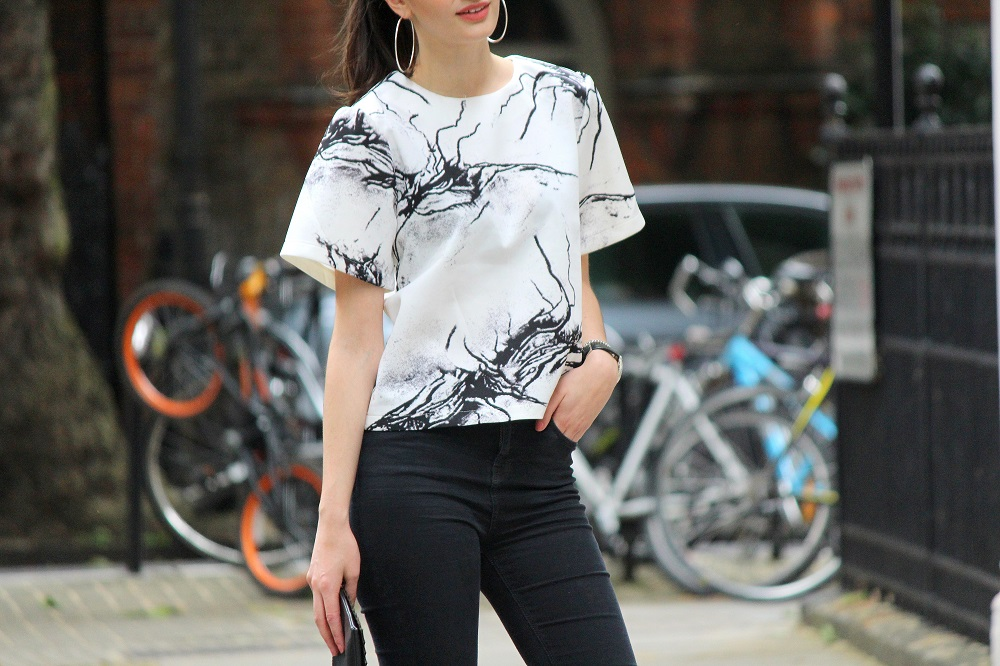 peexo fashion blogger wearing ink print top and ripped black jeans and clutch