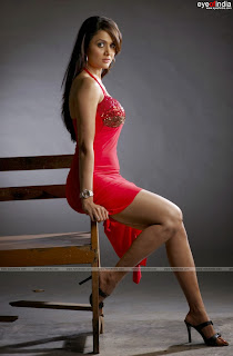 Amrita Arora showing her curvers in a red dress sitting on a bench