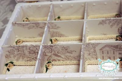 www.bibelodeluxo.com.br CAIXA DE RENDA PERSONALIZADA PARA TOALETE DE CASAMENTO O Bibelô de Luxo personalizou esta romântica caixa com o bordado do monograma do casamento na área interna da tampa, seguindo o planejamento da identidade visual, que também contemplou a utilização do monograma dos noivos em cada um dos itens que compuseram o kit toalete, que foi disposto dentro desta caixa, organizados pelas divisórias da caixa que foram todas forradas com o tecido de toile de jouy, também utilizado em outros elementos do casamento. A delicada renda escolhida para dar um ar mais romântico, juntamente com o floralzinho e o toile de jouy, ornaram com o laço chanel também na cor off white que complementou ainda mais o charme desta charmosa caixa de casamento. Lindíssima, na cor off white, o destaque do acabamento além da renda utilizada no lado externo, e estofamento da tampa, foram os delicados acabamentos utilizados dentro de cada divisão interna.